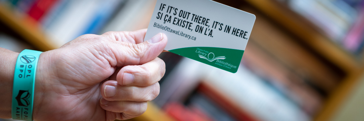 A hand holding a Library card and wearing a green OPL friendship bracelet.