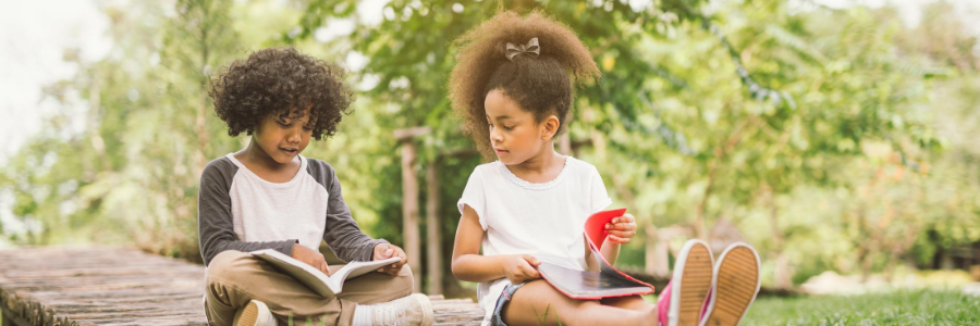 Picture of 2 siblings reading books outside.