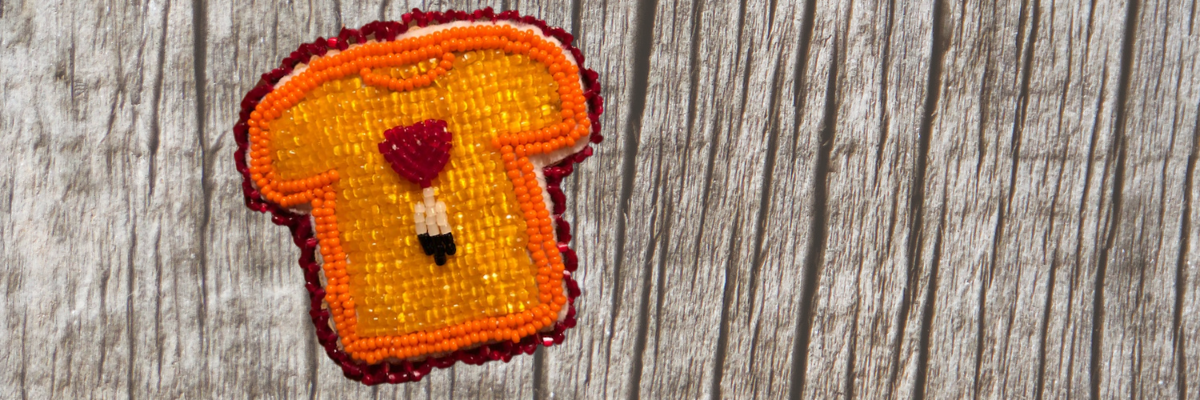 Orange shirt day pin made by indigenous artist with wood in the background