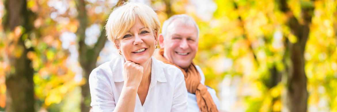 senior couple smiling and sitting on a park bench.