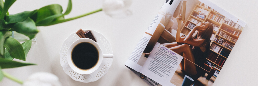 open magazine on a table with a cup of coffee.
