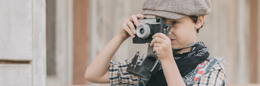 child taking photos with a camera