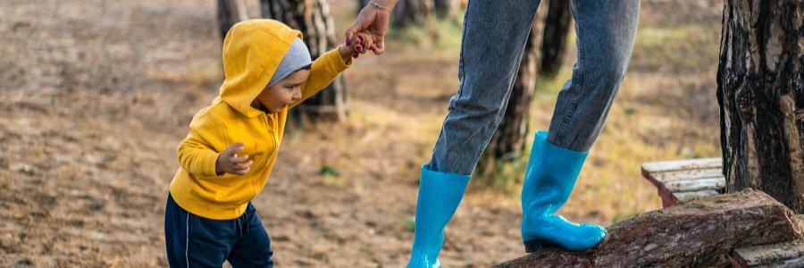child and parent climbing up a log ramp