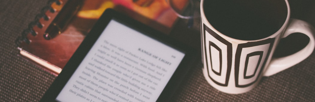Picture of an eBook on a table with a mug.