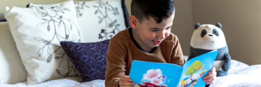 Young boy reading book sitting up in bed with stuffed Panda