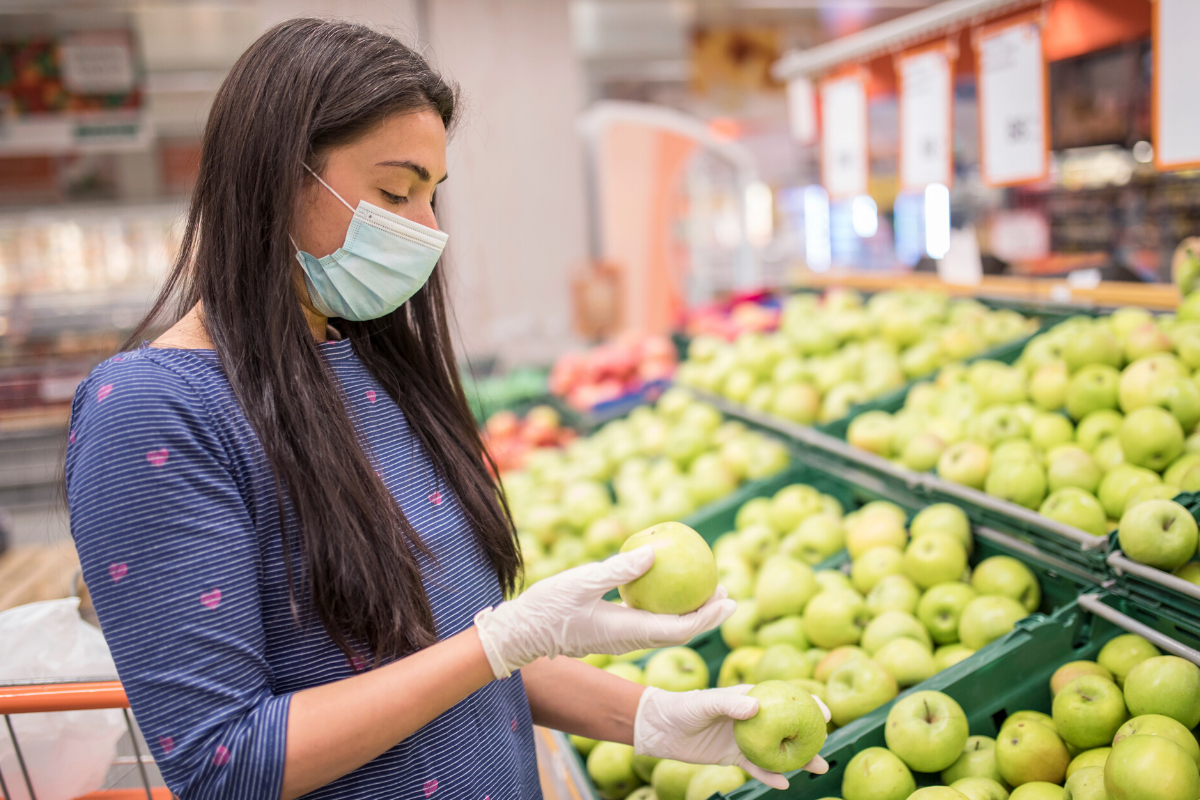 Woman Wearing a Mask in a Grocery Store Picking Apples