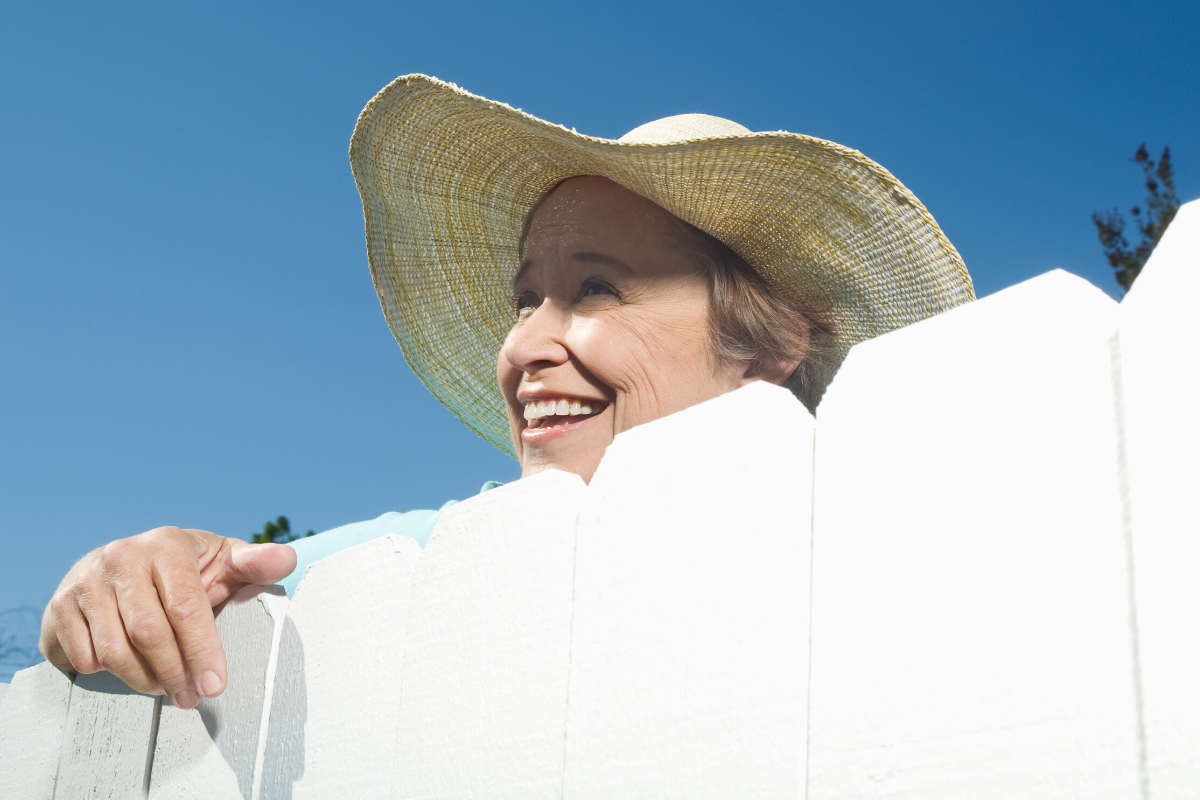 Older woman with a hat on standing by fence
