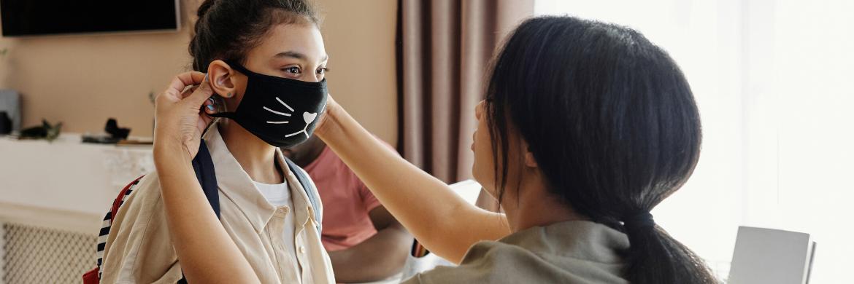 mother adjusting a face mask on her daughter.