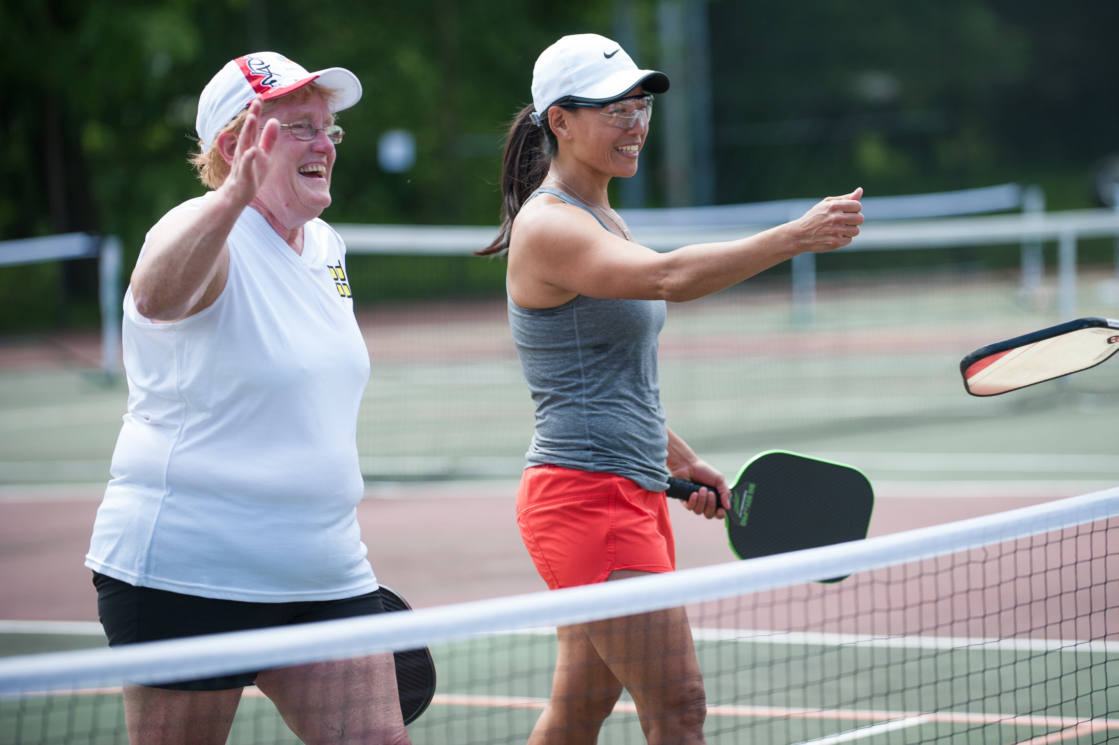 A photo of two women reaching to shake hands after a game of Pickleball