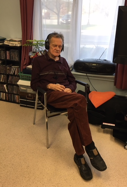 Image of a person listening to music with headphones while seated in a chair