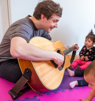 Photo of one of the member of Monkey Rock Music sitting cross legged on the floor, playing guitar for a group of babies and their caregivers