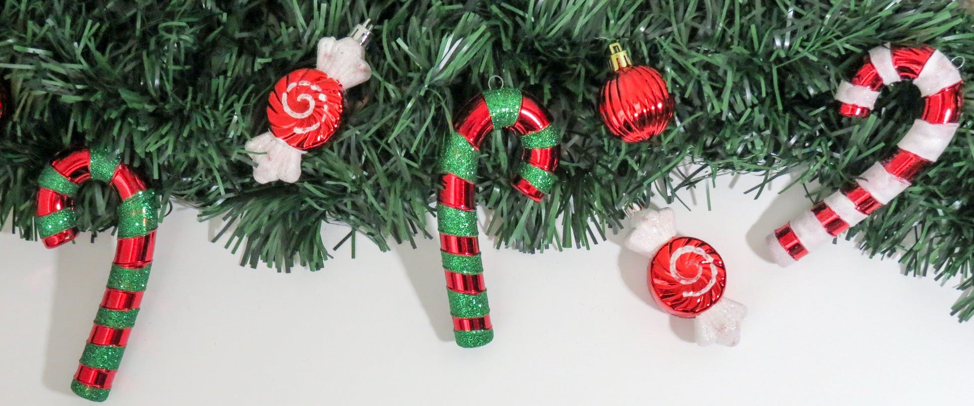 This is an image that shows a holiday garland with candy canes and ornaments.
