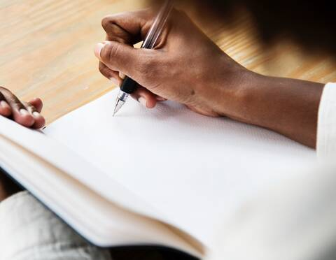 Photo of a person writing in a journal