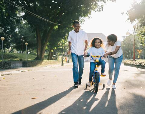 Photo of family with child riding a bicycle
