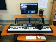 Photo of music editing station, with music keyboard, Mac Pro, monitor and accessories.