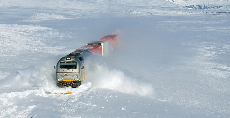 """CargoNet Di 12 """"Euro 4000"""" plowing through snow drifts at about 100 km/h. The train is an intermodal freight train from Bodø towards Trondheim. The picture was taken on the Saltfjellet between Lønsdal and Bolna, Norway."""