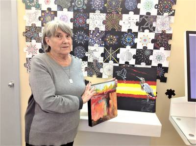 Sheila King displaying two samples of her artwork in front of the puzzle art display.