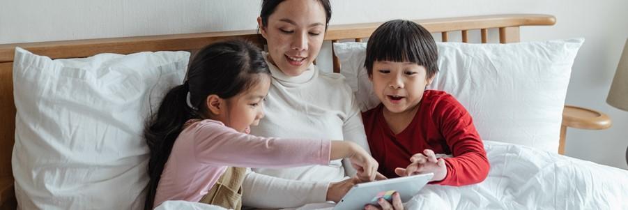 A mother sitting on her bed with her two children reading a book. / Une mère assise sur son lit avec ses deux enfants en train de lire un livre.
