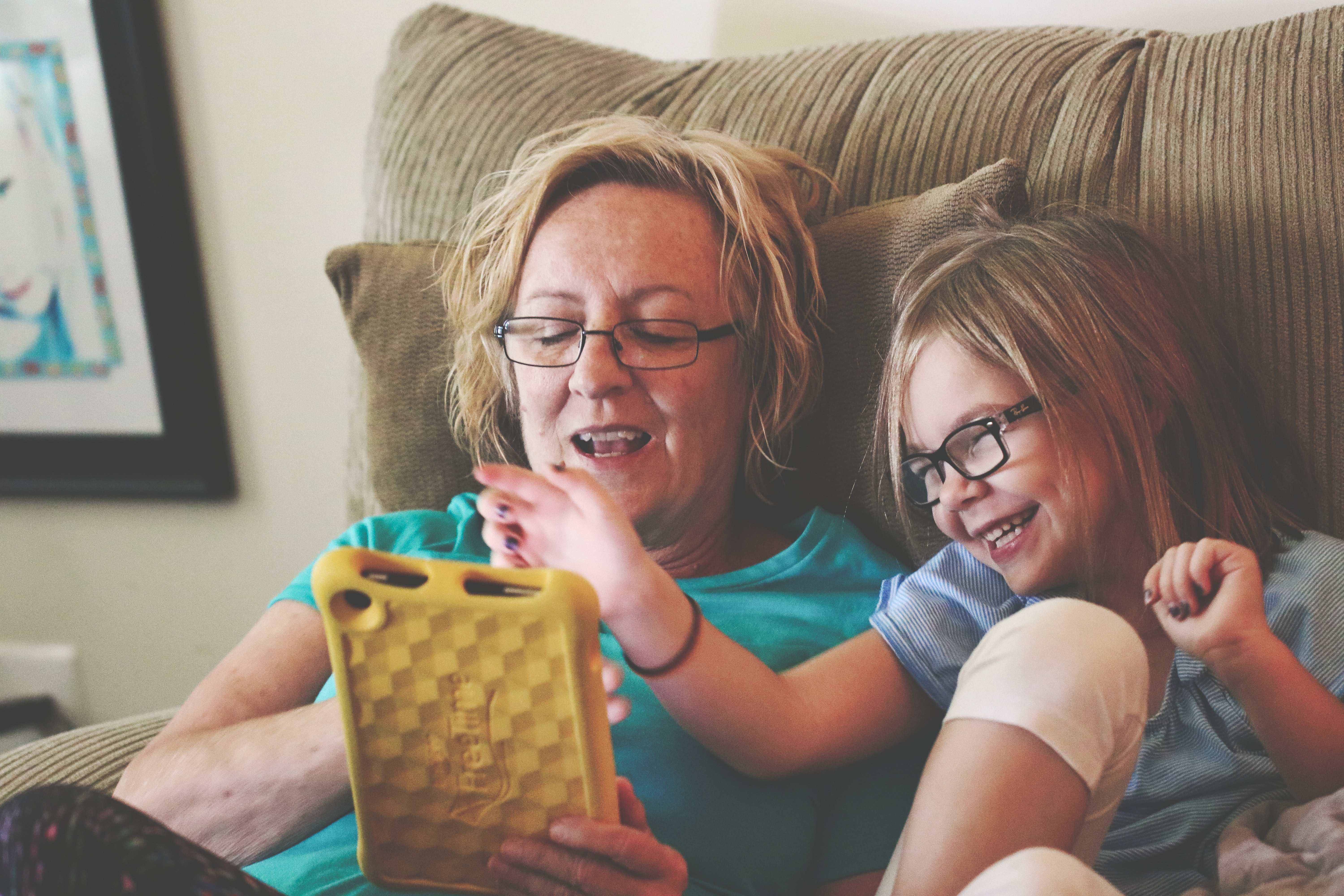 Woman and girl laughing together while using a tablet